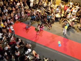 folla di persone assiste ad una sfilata per strada durante una manifestazione